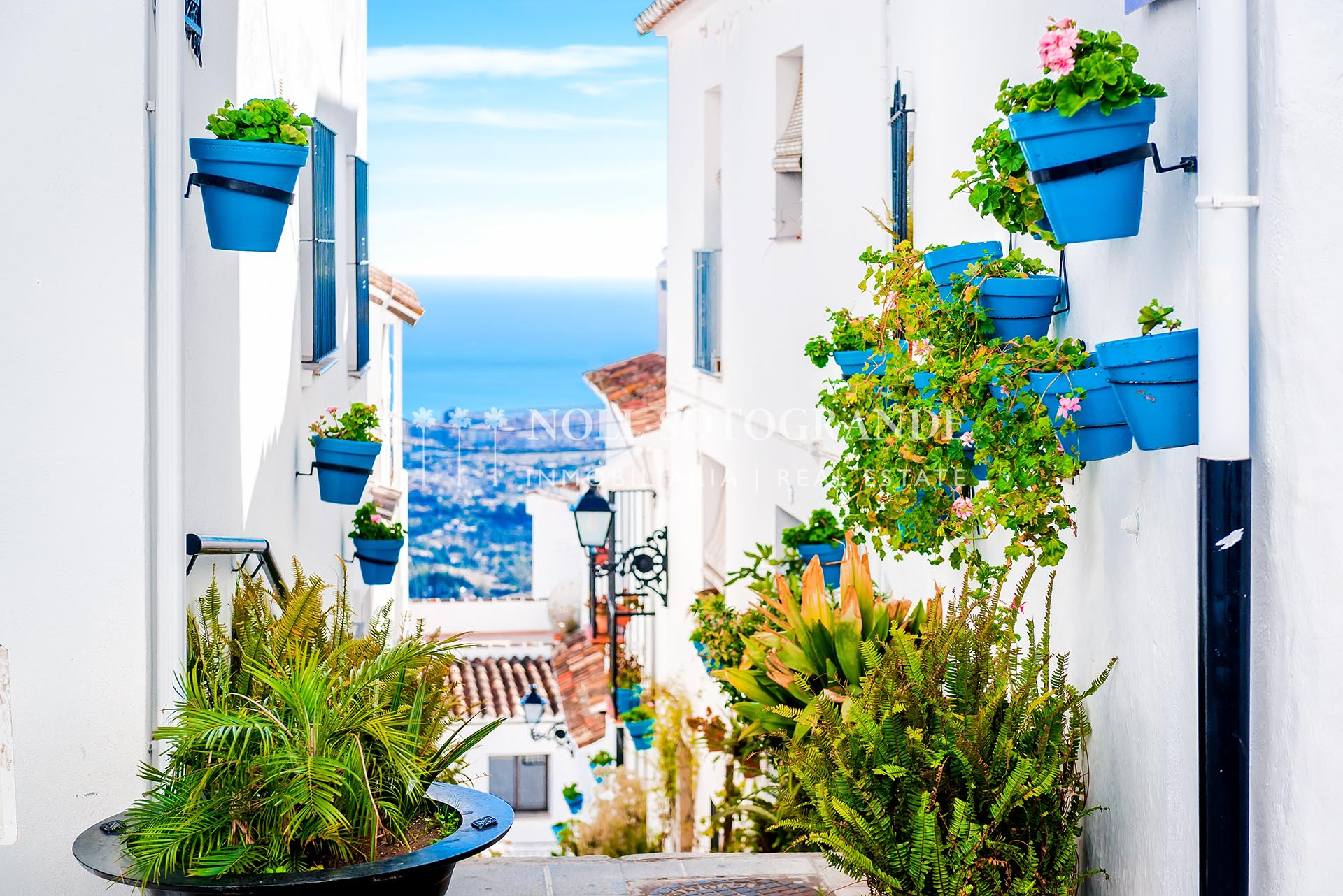 Picturesque street of Mijas with flower pots in facades